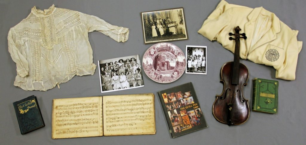 photograph of Salem artifacts such as clothing sheet music and violin